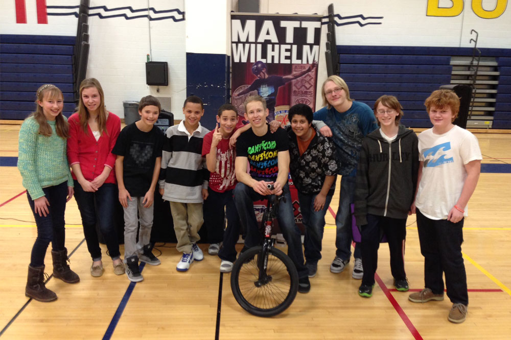 Matt Wilhelm posing with students after speaking about bullying and kindness at a school assembly.