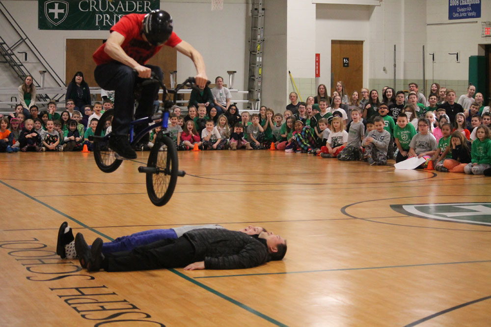 Matt jumping over Father John and a 3rd grade teacher at St. Joseph Catholic School.